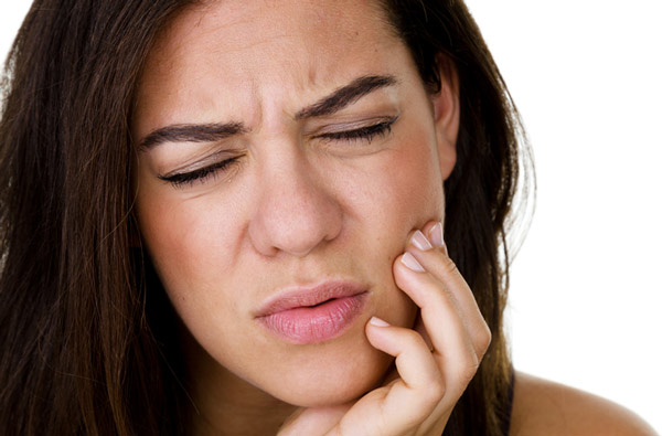 Woman holding jaw due to TMJ pain which can be remedied at Riverwind Dental in Richmond, VA